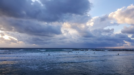 Group of surfers silhouetted with colourful evening sky and sea background, Mediterranean seacoast, Haifa, Israel
