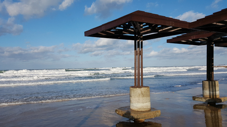tempest: Beach sunshades constructions damaged by water after storm, daylight, clouds, beautiful sky and seashore of Mediterranean Sea, Haifa, Israel Stock Photo