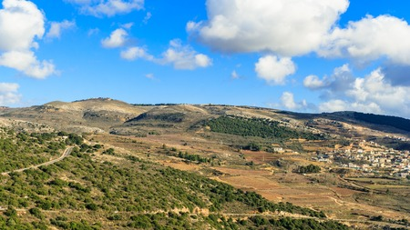 Upper Galilee mountains landscape, Golan Heights nature view from Nimrod, beautiful sunny day, blue sky with white clouds, druze village, Israel. Concept: discover travel destination
