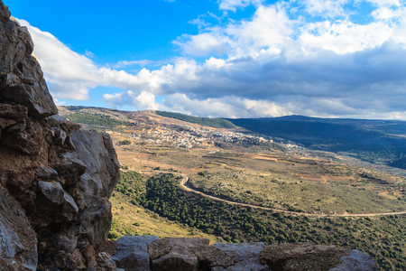 Upper Galilee mountains landscape framed by stones, rocks and ruins of ancient fortress, Golan Heights background, beautiful sky with white clouds, Israel view. Concept: travel, history and nature