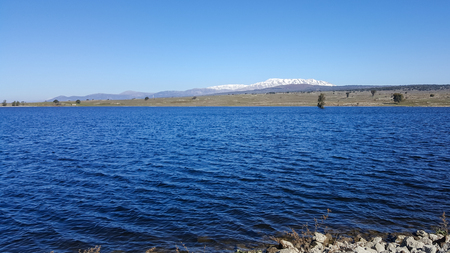 Panoramic beautiful landscape of blue water lake and mountain Hermon as background, Golan Heights, Israel