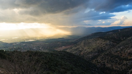 Magnificent landscape of the Golan Heights, the rays of the setting sun make their way through heavy clouds and dispersing the darkness above the valley Stock Photo