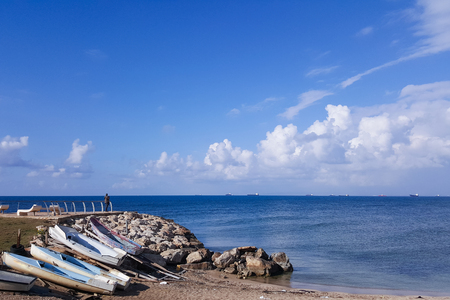 parting the sea: A lone man is standing on a breakwater and staring into the distance. Old boats lie on the shore of the Mediterranean Sea.