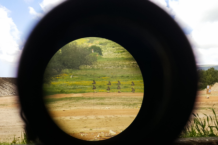 A look through an optical sight aimed at a group of potential targets at the range, outdoor shot, Israeli army IDF training zone Stok Fotoğraf - 82270818