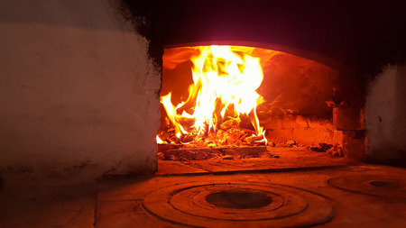 Flames, fire and coals burning in the village home oven. Domestic kitchen. Red and Orange colors prevail
