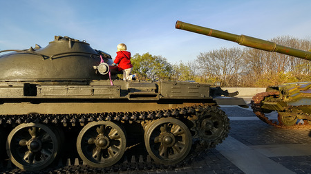 Boy climbs the armor of a military tank, Kiev, Ukraine