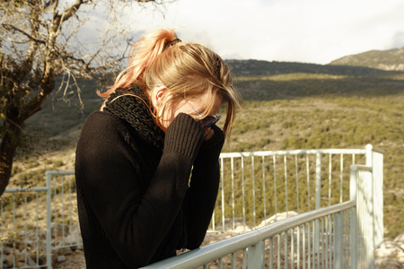 Young woman covers her eyes with hands. Standing on the mountains viewpoint Stock Photo
