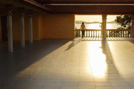 A girl takes pictures of her girlfriend against the sunset in a Buddhist temple, Thailand Stock Photo