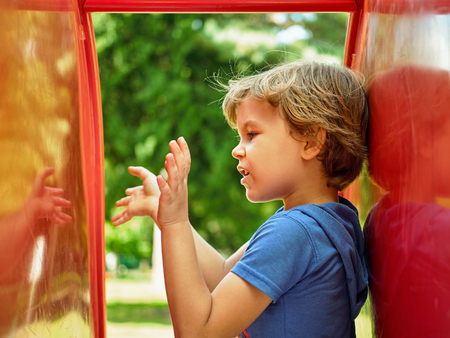Cute little boy is playing with his reflection in childrens slide on the playground. Conducts a conversation with an imaginary friend
