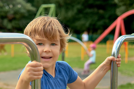 Cute little boy is playing on the playground. Smiling, blonde hair, blue shirt Stock Photo