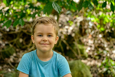 Portrait of a boy 6 years old cheekily smiles against a background of green foliage outdoor, blue shirt, blonde hair,