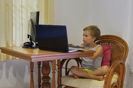 Ragazzino nella stanza domestica, utilizza il laptop del computer, concentrato e guarda negli schermi, si siede sulla poltrona. Mani sulla tastiera. Mobili in stile thailandese