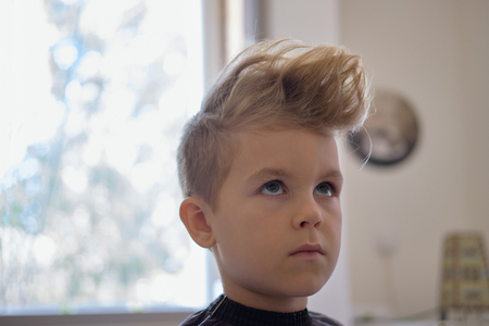 Cute little boy with hairstyle, sitting at home Фото со стока