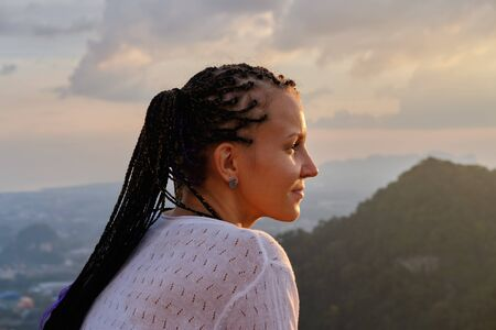 Young woman looking at amazing sunset in mountains. Cornrows hairstyle Stock Photo