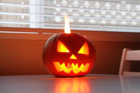 Halloween holiday celebration symbol, pumpkin on kitchen table glowing
