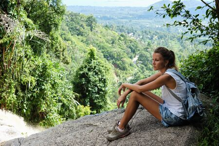 Young caucasian woman sitting on rock uphill in jungle, looking at view