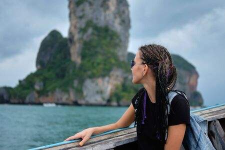 Young woman sitting in longtail taxi boat, looking seascapes in Thailand