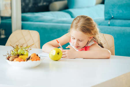 a little girl at the table with a notebook, doing homework and snacking on a fresh Apple. Stockfoto