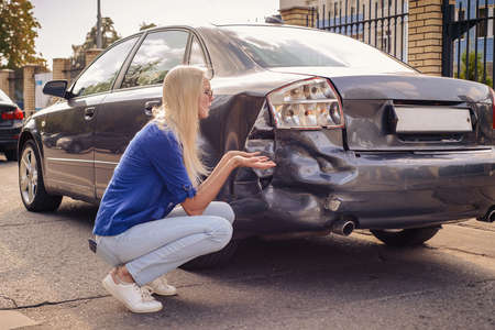 The girl sits at the broken car and thinks what to do. Foto de archivo