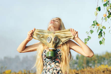 A girl in a dress walking in nature wears a gas mask. The concept of environmental pollution, viruses, and epidemics. Imagens