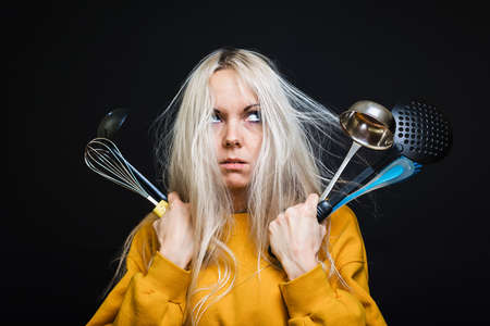 A young girl with disheveled hair holds kitchen tools, arrives terrified of not being able to cook anything. The concept of a young housewife.