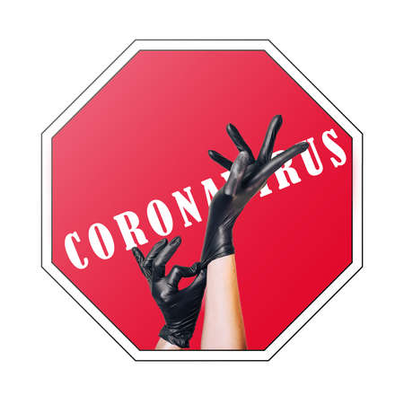 Hand in a black medical glove raised up against the background of a stop sign with the words coronavirus. Stockfoto
