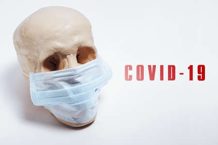 A skull in a medical mask on a white background with the inscription covid-19. The concept of an epidemic , an unknown virus.