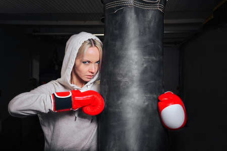 A young girl in Boxing gloves and a stern look poses with a pear in the gym.