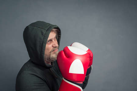 Portrait of a guy in a hoodie and Boxing gloves taking a protective stance.