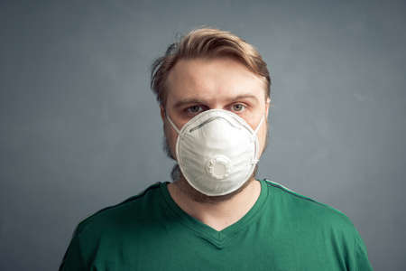 Portrait of a young blond guy in a protective respirator on a gray background.