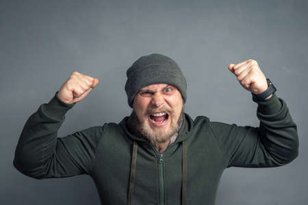 Portrait of a bearded guy in a hoodie and hat with his hands raised and clenched fists shouting Yes. The concept of luck, leadership, and winning.