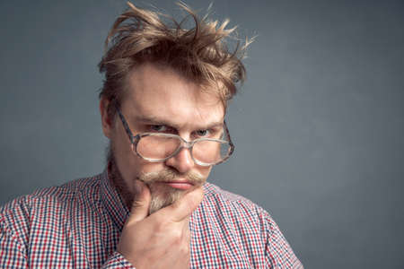 A portrait of a bearded nerd with a disheveled hairdo, gazing thoughtfully through his large glasses, scratching his chin.