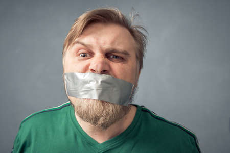 A bearded man with duct tape over his mouth. The concept of censorship.