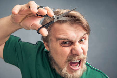 An irritated bearded man wants to cut off his bangs with scissors. The concept of changing the style. 版權商用圖片