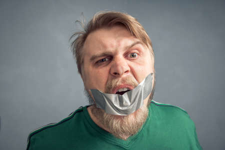 A close-up portrait of a bearded man with his mouth taped shut. The concept of what can't be said is censorship. 版權商用圖片