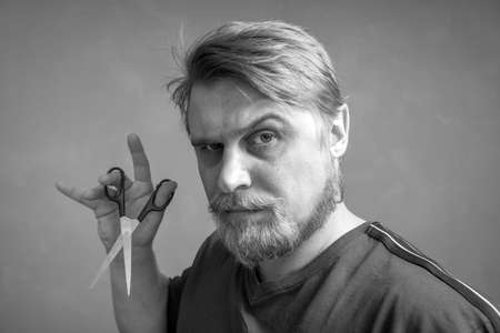 Close-up of a bearded blond man with a pair of scissors in his hand. The concept of self-care for the hair style change and hair salon. black and white photo.