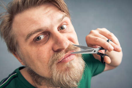 Close-up of a bearded man with scissors cutting his mustache. The concept of self-care for facial hair.