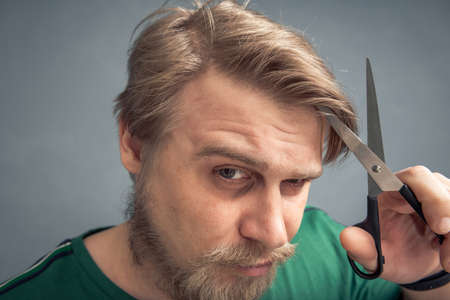 Close-up of a bearded man with scissors cutting his hair. The concept of independent hair care, style changes.