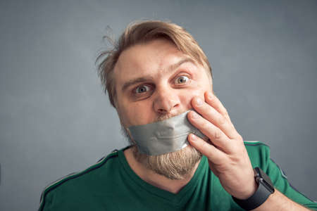 A bearded man with duct tape over his mouth. The concept of censorship. 版權商用圖片