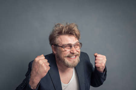 A portrait of a bearded guy with glasses, tousled hair, clenched fists, and a contented face with a grin. The concept of luck, leadership and victory, success. 版權商用圖片