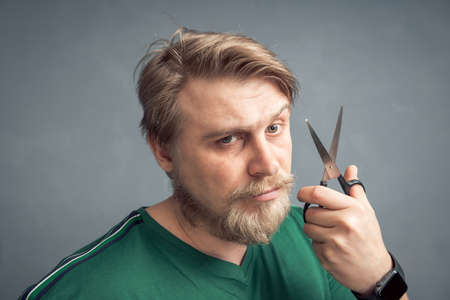 Close-up of a bearded blond man with a pair of scissors in his hand. The concept of self-care for the hair style change and hair salon. 版權商用圖片
