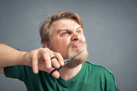 An irritated man wants to cut off his beard with scissors. The concept of changing the style.