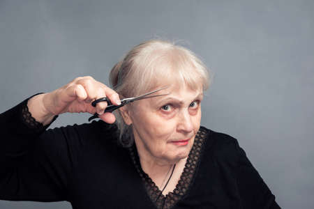 An elderly woman with a pair of scissors in her hand on a gray background. Barber services. The job of a hairdresser with sharp scissors. The concept of a Barber shop. Women's haircut. 版權商用圖片
