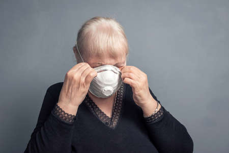 An elderly woman in a medical mask, on a gray background. Studio portrait of an adult looking at the camera flu epidemic, Allergy to dust, protection from the virus. 版權商用圖片