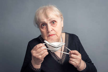 An elderly woman puts on a medical mask, on a gray background. Studio portrait of an adult looking at the camera flu epidemic, Allergy to dust, protection from the virus.