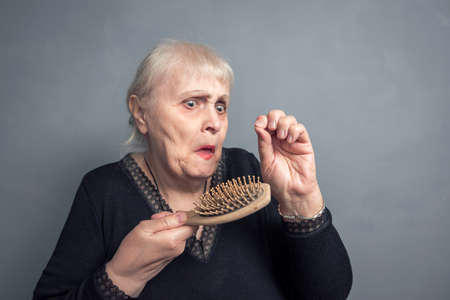 An elderly woman with a comb in her hand and a surprised look on a gray background. Barber services. The concept of a Barber shop. Women's haircut, hair salon. Comb hair.