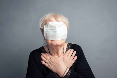 An elderly woman with a medical mask over her eyes on gray