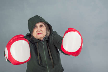An elderly woman in Boxing gloves on a gray