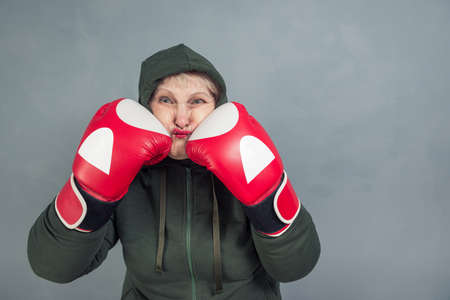 An elderly woman in Boxing gloves on a gray background. The concept of fighting, winning, fighting spirit, sports.