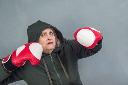 An elderly woman in Boxing gloves on gray